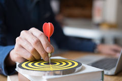 Business Man hand holding a target with darts hitting the center. Business Man hand holding a target Royalty Free Stock Photos