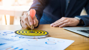 Business Man hand holding a target with darts hitting the center. Business Man hand holding a target Stock Images