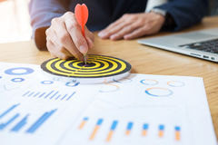 Business Man hand holding a target with darts hitting the center. Business Man hand holding a target Stock Photos