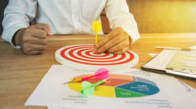 Business Man hand holding a target with darts hitting the center. On wood table Royalty Free Stock Image