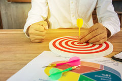 Business Man hand holding a target with darts hitting the center. On wood table Stock Photography