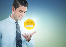 Business man with hand open and emoji with flare against blue green background Royalty Free Stock Photography