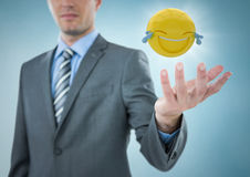 Business man with hand out and emoji with flare against blue background Royalty Free Stock Photos