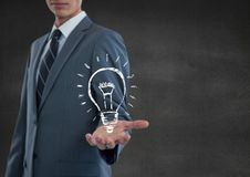 Business man hand out with lightbulb doodle against grey wall Stock Image