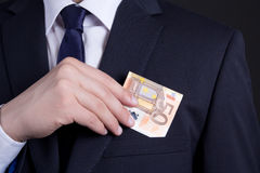 Business man hand putting euro banknote into suit pocket Stock Photos