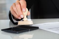 Business man hand with rubber stamp Royalty Free Stock Photos