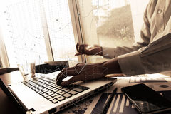 Business man hand working on laptop computer on wooden desk as c. Business documents on office table with smart phone and digital tablet and graph business Stock Photo