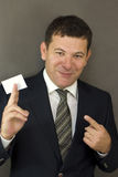 Business man handing a blank. Business card over gray background Stock Photography