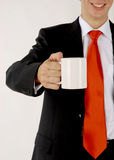 Business man handing a blank mug. There is men shows his empty cap, where you can put logo and information of your company. He smiles stock image