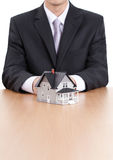 Business man hands behind house model Royalty Free Stock Image
