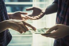 Business man handing money over a business dealing royalty free stock photos