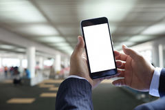 Business man hands hold mobile blank screen of smart phone. At airport lounge in airport terminal Stock Images