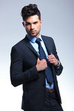 Business man with hands on lapels. Young business man holding his jacket by its lapels and looking at the camera. on a gray background Stock Photos