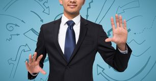 Business man with hands out against blue background with arrow graphics Stock Photography