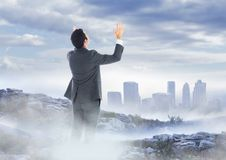 Business man hands up on misty mountain peak against skyline Royalty Free Stock Images
