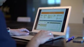 A business man hands using a laptop with stats stock footage