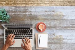 Business man hands using a laptop on workplace. With a cup of coffee,pencil and notebook vintage hipster wooden desktop top view with copy space. Business Stock Photo