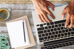Business man hands using a laptop on workplace. With a cup of coffee,pencil and notebook vintage hipster wooden desktop top view with copy space. Business Stock Image