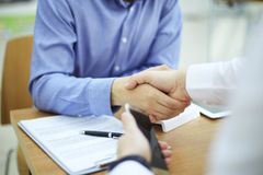 Business man handshake. In modern office after good deal Stock Photos
