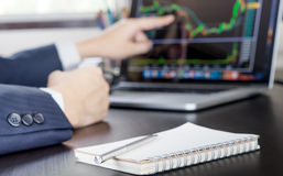 Business Man happily pointing at the stock trading is going up. Royalty Free Stock Images