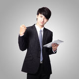 Business man happy using tablet pc. Isolated on gray background, asian model Royalty Free Stock Image