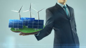 Business man has on hand green energy concept build animation solar panel and windmill stock video
