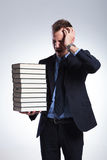 Business man has headache from books Royalty Free Stock Image