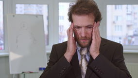 Business man has headache at the office. Attractive caucasian businessman having headache at the office. Close up of handsome middle aged man keeping hands on stock video footage