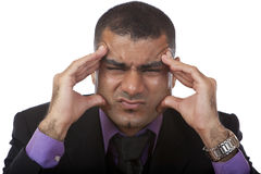 Business man has headache of stress. Closeup of a businessman having a bad headache, because of stress. Isolated on white Stock Image