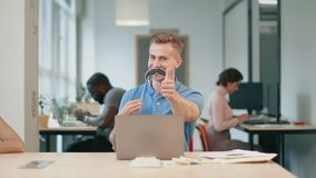 Business man having fun at workplace. Young man winking eye looking at camera stock footage