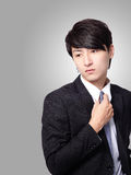Business man having stress and touch his tie. Isolated over gray background, model is a asian male Royalty Free Stock Photography