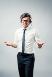 Business man with head-set. Businessman pointing gestures having a conversation with head-set Royalty Free Stock Image