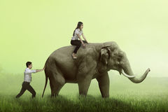 Business man help pushing elephant while his friend sit on it Stock Images