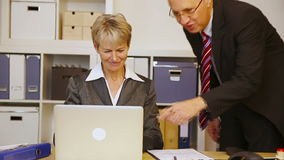 Business man helping woman in office stock video footage