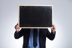 Business man hides behind blackboard Royalty Free Stock Image