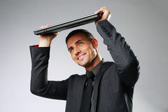 Business man hides under the laptop Stock Photo