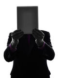 Business man hiding behind  digital tablet silhouette Stock Image