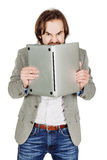 Business man hiding behind his laptop computer in his hands. emo Royalty Free Stock Photography