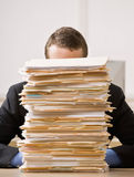 Business man hiding behind tall stack of folders Stock Images