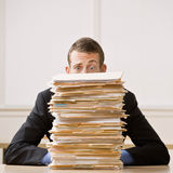 Business man hiding behind tall stack of folders Royalty Free Stock Image