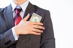 Business man hiding money in jacket pocket Royalty Free Stock Images