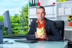Business man at his desk with piggy bank looking dissatisfied Stock Photo