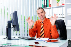 Business man at his desk showing alright. Young business man at his desk showing alright stock image