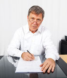Business man at his desk. Business man signing a contract at his desk Royalty Free Stock Photo