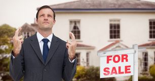Business man with his fingers crossed, property sale Royalty Free Stock Images