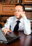 Business man in his office on a laptop Stock Images
