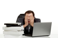 Business man in his office stressed. Business man stressed out in his office with a lap top and a lot of papers in front of him holding his head and eyes Royalty Free Stock Photography