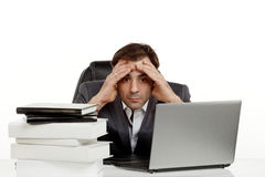 Business man in his office tired. Business man stressed out in his office with a lap top and a lot of papers in front of him holding his head and looking in one Stock Images