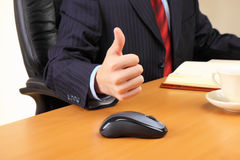 Business man at his workplace hold thumbs up. Stock Image