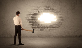 Business man hitting brick wall with hammer and opening a hole Royalty Free Stock Images
